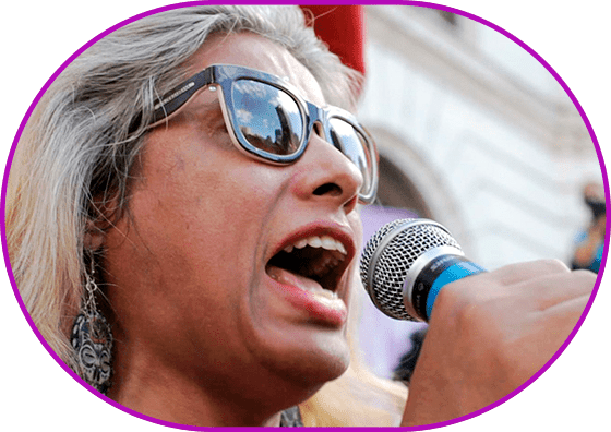 """Still from the film """"Indianara"""". Close-up shot. Outdoors, white wall, red flags. In the foreground a grey-haired woman wearing sunglasses shouts in the microphone. Fists are raised."""